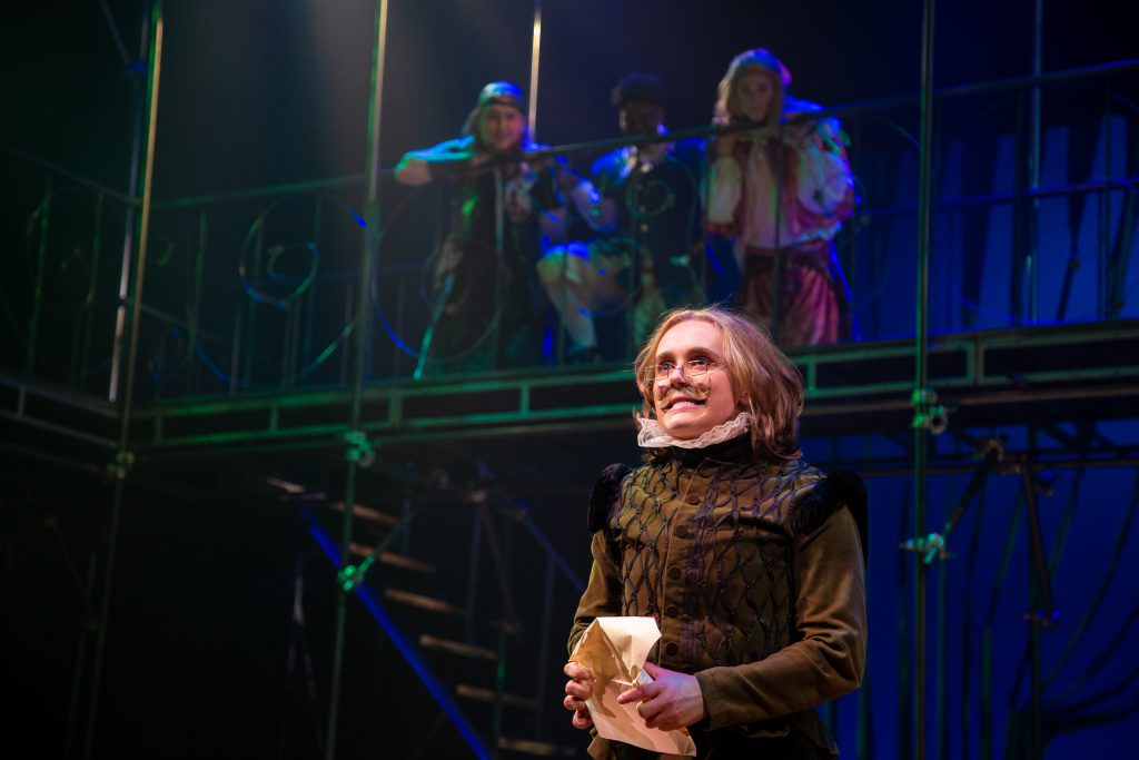 Actor intensely looking at the audience with three actors on a balconey above in the 2019 production of Twelfth Night