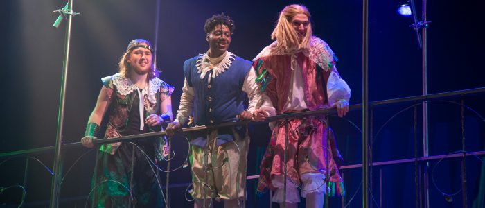 Three actors looking down from a balcony in the 2019 production of Twelfth Night