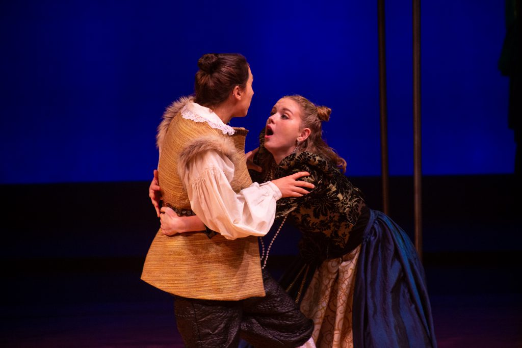 An actor holding the waist of another actor in Twelfth Night