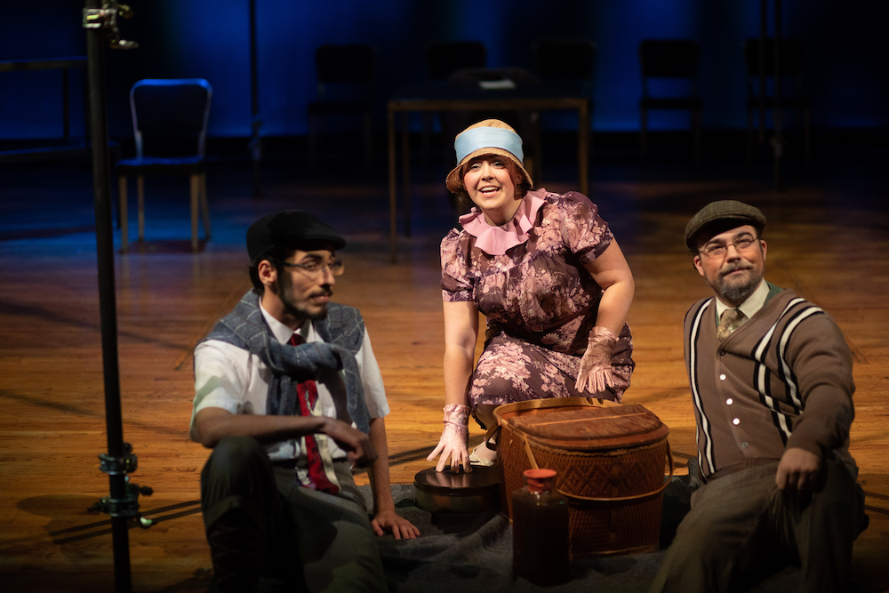 Three actors sitting on the ground of a picnic in the 2018 production of It Can't Happen Here