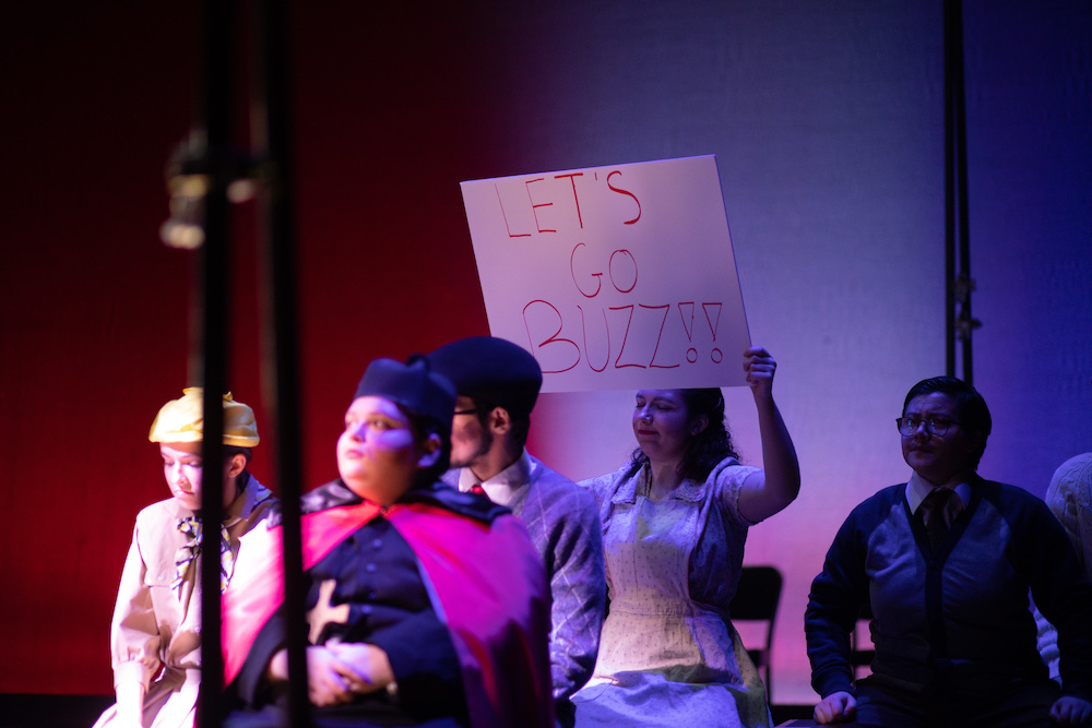 "Actor holding a sign saying ""Let's Go Buzz"" in the 2018 production of It Can't Happen Here"