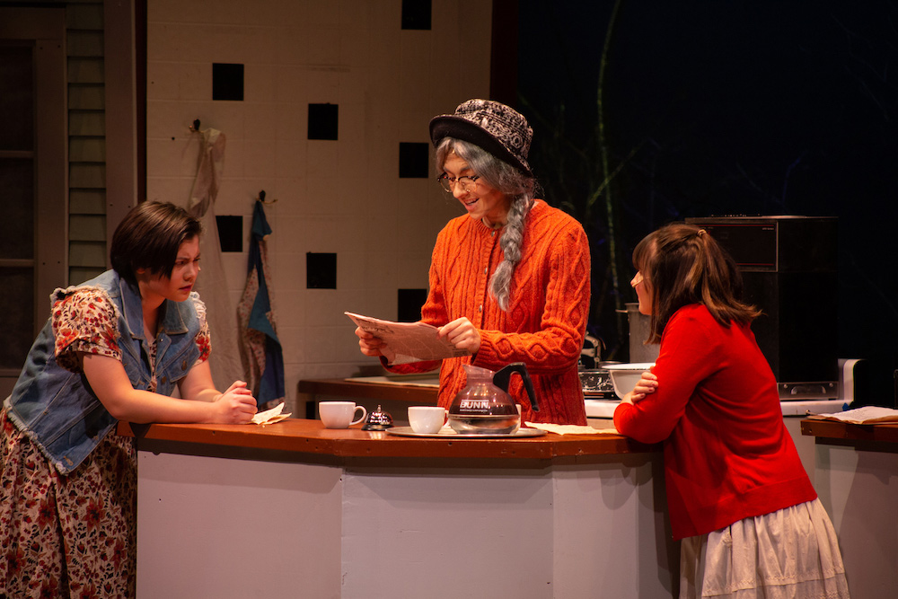 Actor reading a newspaper to two other actors in the 2019 production of Spitfire Grill