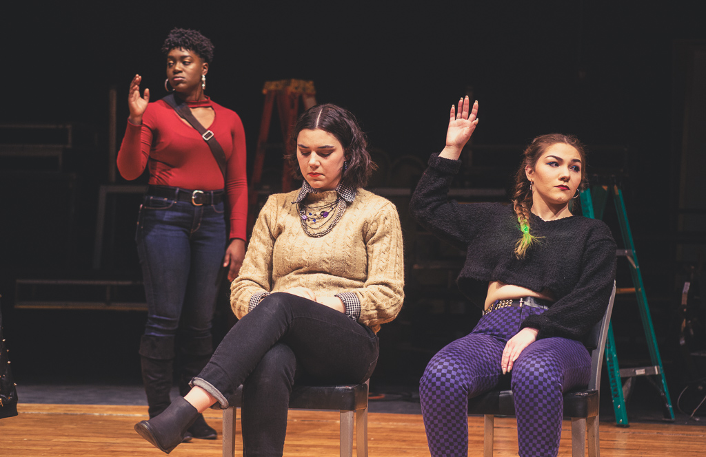 Three actors in the play Student Body. Two of them are raising their hands in a vote