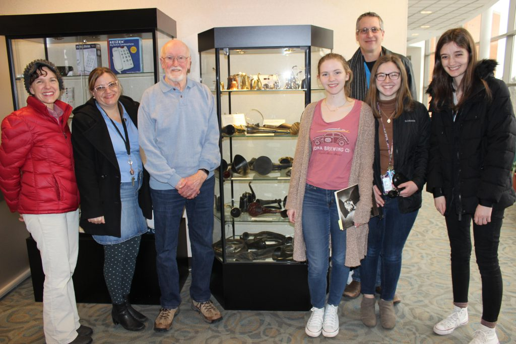 Group Photo at the Department of Audiology at Western Michigan University. The group is posing around a case of ear trumpets.