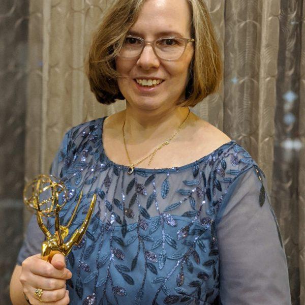 Alumna Kate Loebrich holding an Emmy