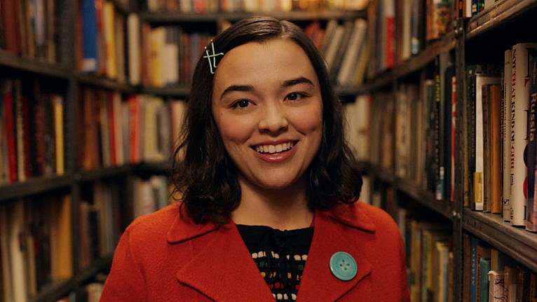 a smiling actor wears a red jacket. there are book shelves behind her.