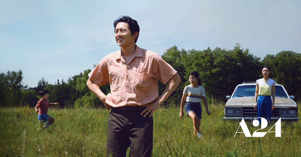 Yeun and co-stars standing in an open field