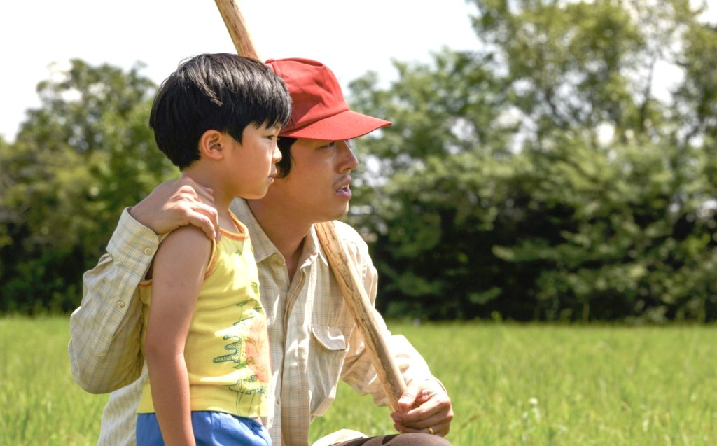 Yeun with his arm over a young boy
